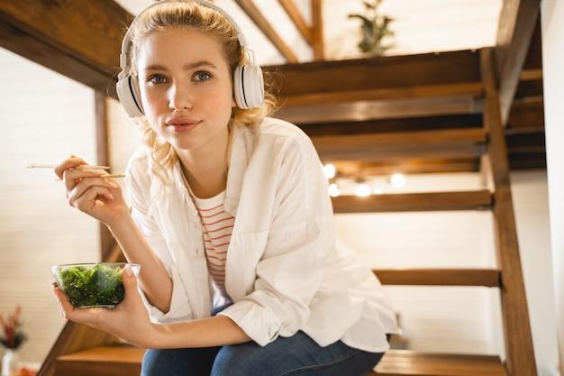 En train de te regarder. heureuse femme assise sur des escaliers en bois tout en mangeant des algues