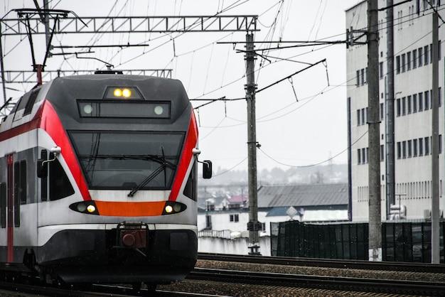Un train de voyageurs à grande vitesse circule sur les voies ferrées de la ville
