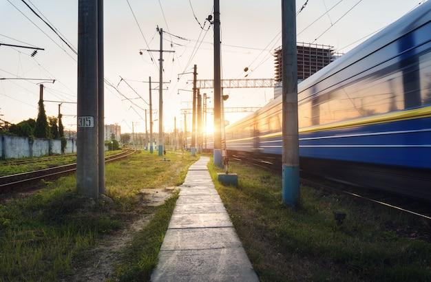 Train de voyageurs à grande vitesse en mouvement sur la voie ferrée au coucher du soleil