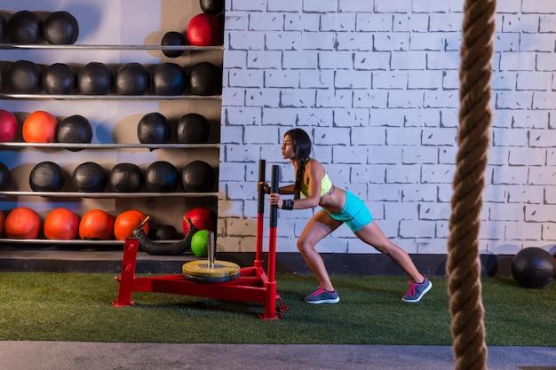 Traîneau, femme, pousser, poids, séance d'entraînement