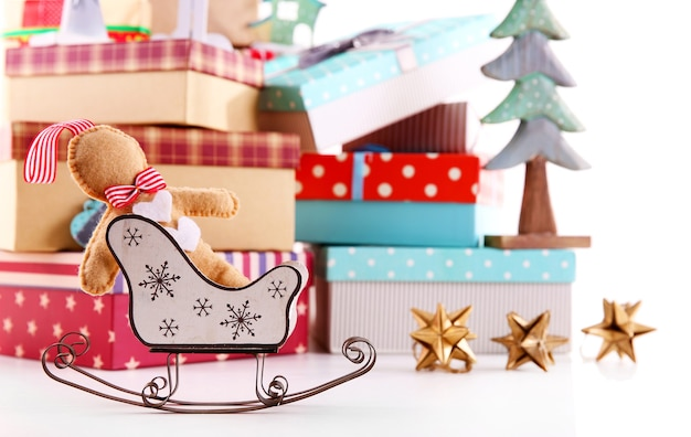 Traîneau sur fond de beaux cadeaux de noël avec des jouets isolés sur blanc
