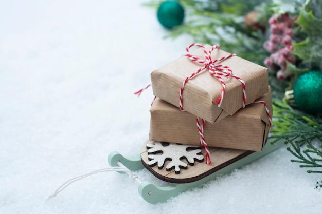 Traîneau de noël avec des coffrets cadeaux sur la neige. carte de voeux d'hiver abstraite.