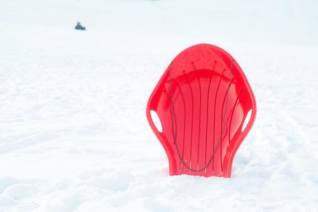 Traîneau en plastique rouge, luge, traîneau sur fond blanc neigeux à l'extérieur.