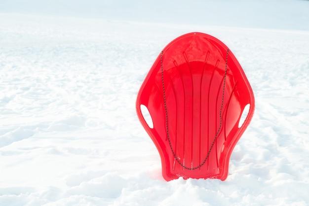 Traîneau en plastique rouge, traîneau, traîneau sur fond blanc neigeux à l'extérieur. jeux et activités d'hiver pour les enfants