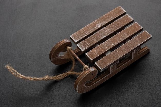 Traîneaux décoratifs en bois sur fond noir invitation de fête de carte de voeux saisonnière