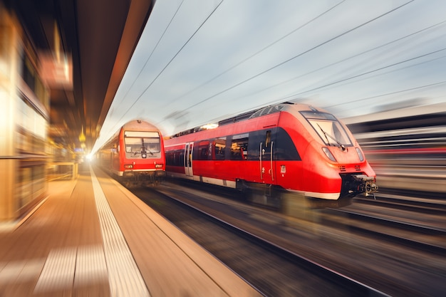 Trains de voyageurs rouges à grande vitesse modernes au coucher du soleil. gare