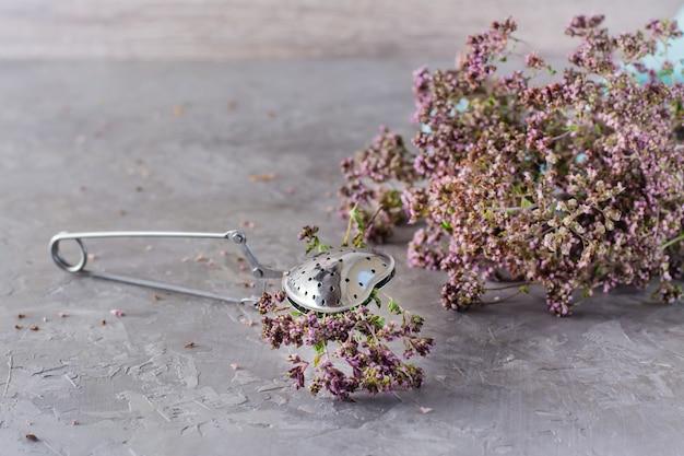Traitement à base de plantes. un bouquet d'origan est serré dans une cuillère à café et un bouquet d'herbes à côté sur la table
