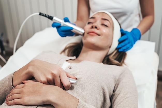 Traitement de beauté du visage d'une belle jeune femme avec de l'oxygène au salon de beauté cosmétique.