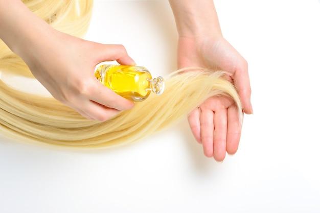 Traitement capillaire à l'huile pour femme aux cheveux blonds sur fond blanc. spa, salon de beauté. soins capillaires dans un salon spa moderne.