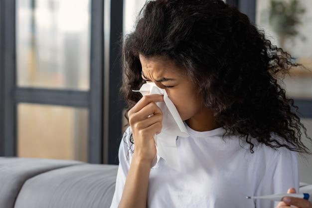 Traitement à domicile. une femme afro-américaine épuisée et malade avec un nez qui coule, des maux de tête et de la fièvre souffle la morve à l'aide d'une serviette. concept de rhume et de grippe