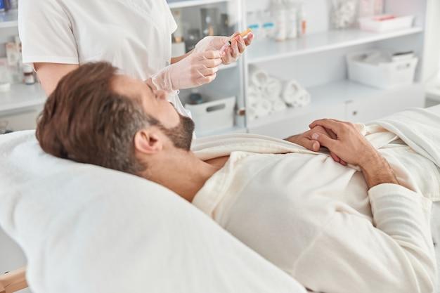 Traitement du jeune homme par une esthéticienne pour raffermir et lisser les rides de la peau du visage. injections de mésothérapie à un homme séduisant.