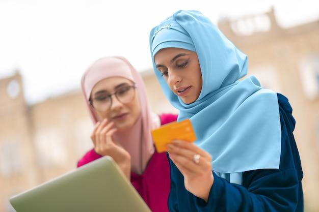Traitement du paiement en ligne. femme musulmane en hijab bleu tenant une carte bancaire lors du traitement du paiement en ligne
