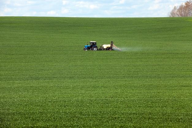 Traitement du tracteur céréalier photographié dans le domaine agricole pendant le traitement des pesticides