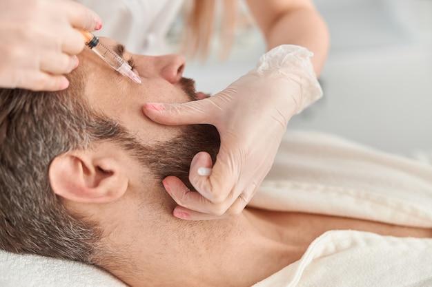 Traitement en gros plan du jeune homme par une esthéticienne pour resserrer et lisser les rides sur la peau du visage. injections de mésothérapie à un homme séduisant.