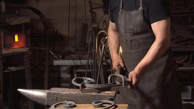 Traitement des gros plans de métaux en fusion. forgeron à la main.