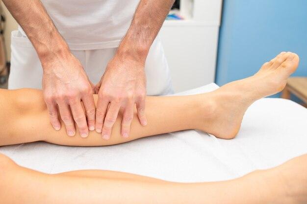 Traitement des jambes d'un athlète par un physiothérapeute