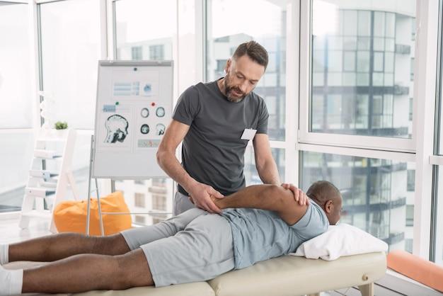 Traitement médical. homme barbu sérieux regardant la main de ses patients tout en le traitant