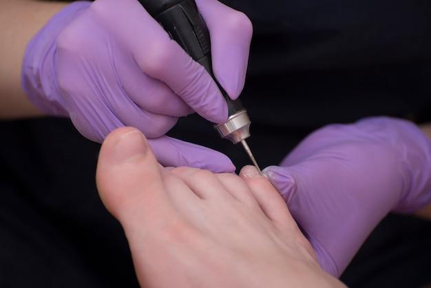 Traitement des ongles, pédicure. mains gantées avec une pédicure. fermer