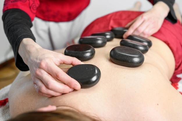 Traitement des pierres. jeune femme allongée sur le devant en profitant d'un massage au spa avec des pierres chaudes sur le dos. concept de traitement de beauté.