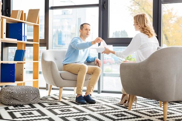 Traitement professionnel. déprimé beau bel homme assis dans le fauteuil et prenant un mouchoir en papier lors d'une visite chez un psychologue