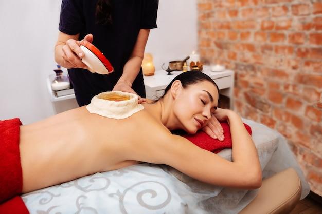 Traitement en salon. femme aux cheveux noirs paisible se détendre sur un canapé pendant que le maître verse de l'huile chaude dans un réservoir sur son dos