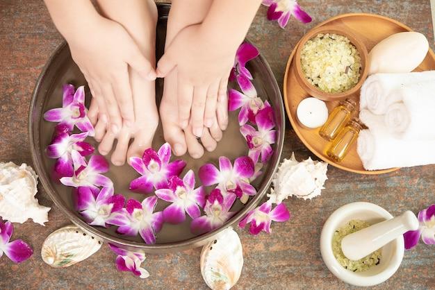 Traitement spa et produit pour pieds féminins et spa pour les mains. fleurs d'orchidées dans un bol en céramique.