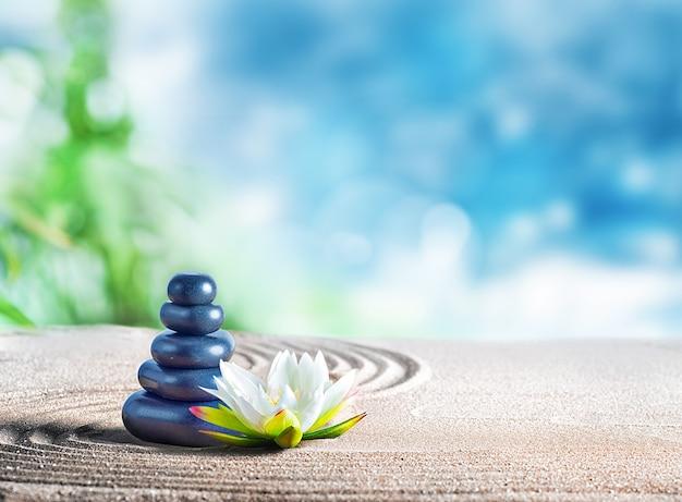 Traitement spa relaxant avec des pierres orientales sur le sable