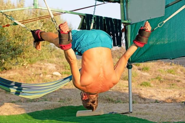 Traitement de yoga pour swing de yoga de base, jeune homme mince attaché à quatre planches au-dessus du sol avec tapis d'exercice, homme développant l'endurance et l'étirement du noyau