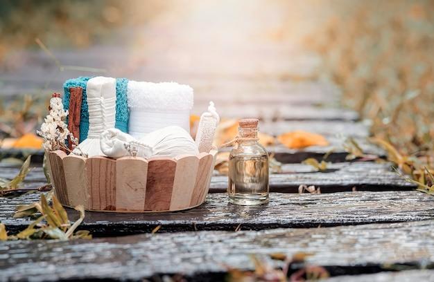 Traitements de spa dans un seau en bois avec balle de compression aux herbes, bouteille d'huile, bougies et serviette sur fond de nature humide.