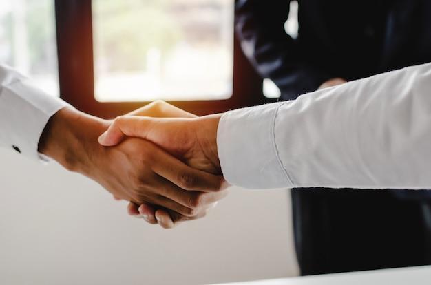 Traiter. groupe de gens d'affaires la poignée de main après avoir terminé la réunion d'affaires