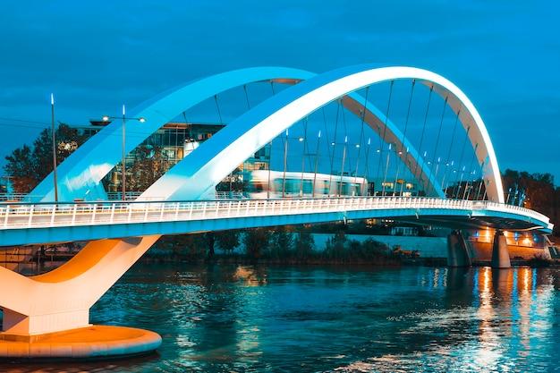 Tramway traversant le pont de nuit, lyon, france.