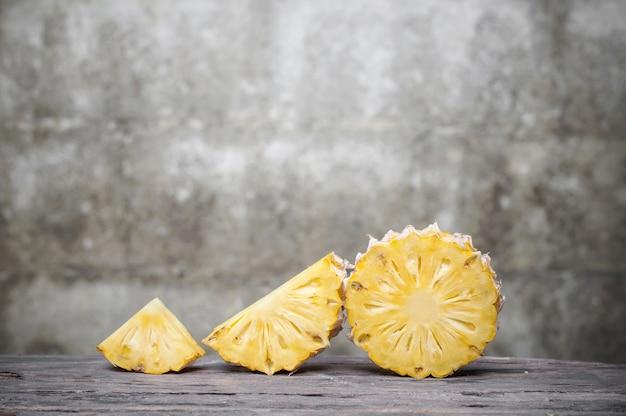 Tranche d'ananas sur une table en bois avec vieux fond de mur de brique