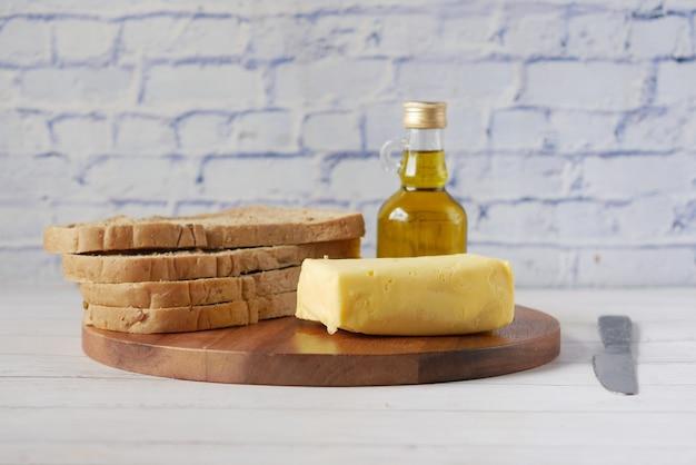 Tranche de beurre et pain complet sur planche à découper
