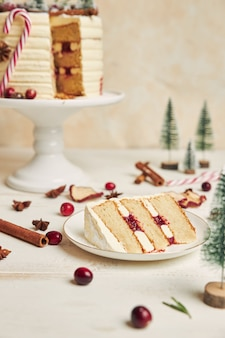 Tranche de biscuit avec des couches de crème sur une assiette et un gâteau derrière
