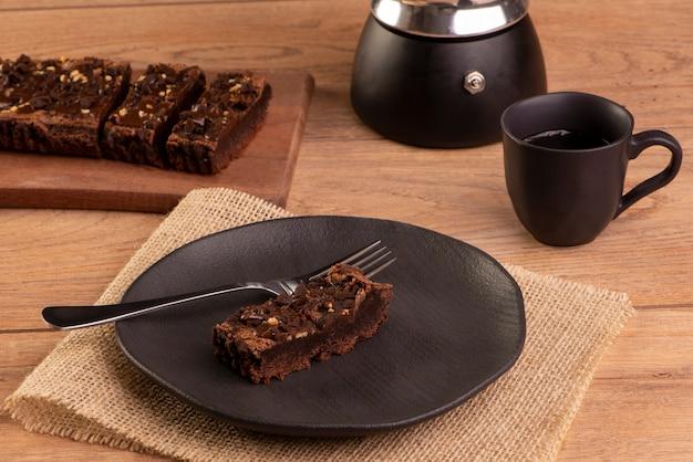 Une tranche de brownie sur une assiette avec une tasse de café sur une table en bois.