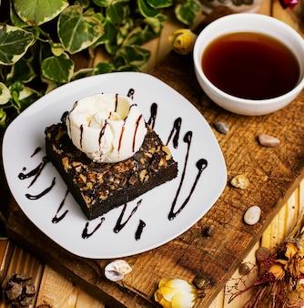 Une tranche de brownie au chocolat avec glace à la noix et à la vanille.