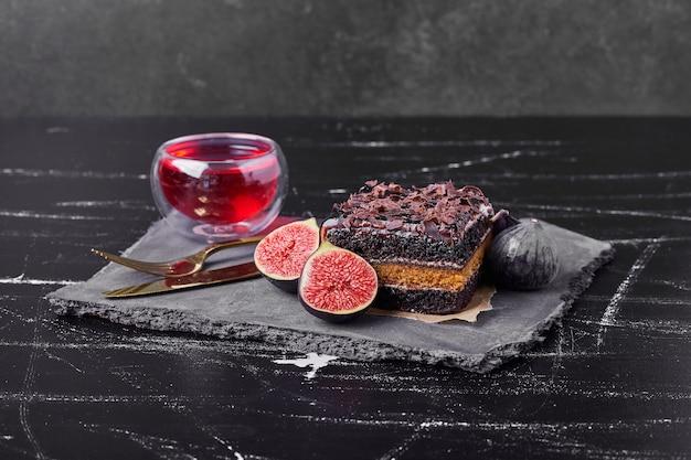 Une tranche carrée de gâteau au fromage au chocolat avec des figues et du vin.