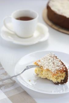 Une tranche de cheesecake à l'ananas et à la noix de coco et une tasse de thé sur la table.