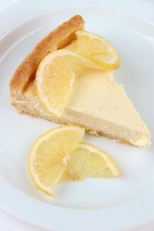 Tranche de cheesecake au citron sur plaque, isolé sur blanc