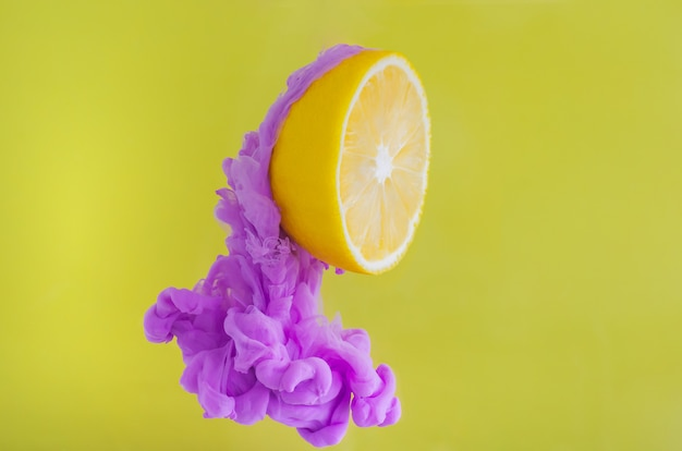Tranche de citron avec une concentration partielle de la dissolution de la couleur de l'affiche violette dans l'eau sur fond jaune.