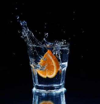 Tranche de citron éclaboussant dans un verre d'eau avec un jet de gouttelettes d'eau en mouvement suspendu dans l'air au-dessus du verre sur un fond sombre.