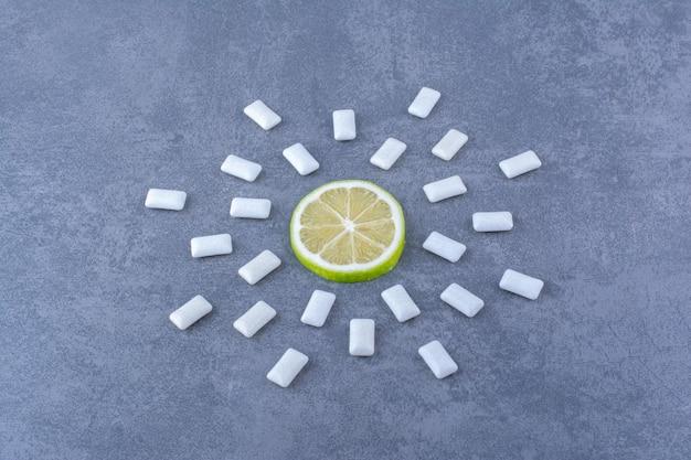 Tranche de citron entouré d'un arrangement de comprimés de bubblegum sur une surface en marbre