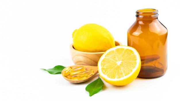 Tranche de citron frais avec des feuilles, supplément de capsule de vitamine c de naturel isolé