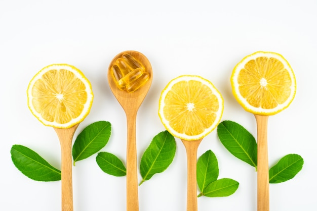 Tranche de citron frais avec des feuilles, supplément de vitamine c de naturel isolé sur fond blanc