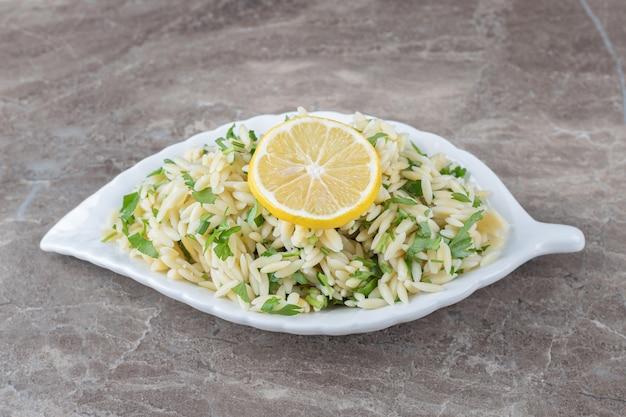 Tranche de citron sur pâtes aux légumes verts, sur le marbre.