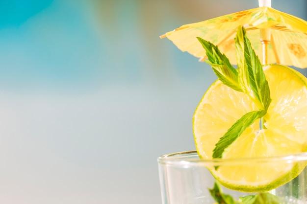 Tranche de citron vert avec feuille de menthe poivrée sous un parapluie