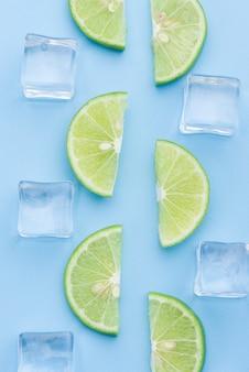 Tranche de citron vert frais avec glaçon sur bleu