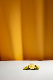 Tranche de citrons verts sur une table blanche devant un rideau jaune