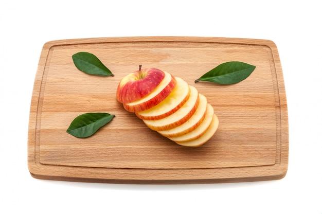 Tranche de délicieuse pomme succulente aux feuilles vertes sur une planche à découper en bois.