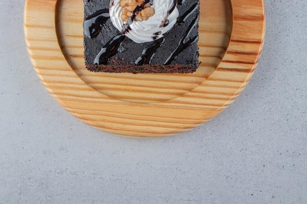 Tranche de délicieux brownie au chocolat avec de la crème sur une plaque en bois. photo de haute qualité
